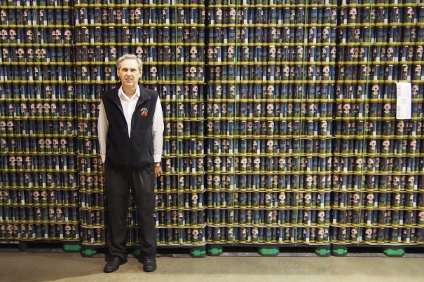 Master Brewer Ken Lee in front of our wall of 155,600 empty IPA cans waiting to be filled.